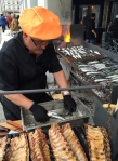 A street vendor cooking sardines.